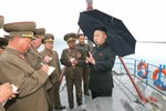 Ảnh: Kim Jong-un vác ô thị sát tàu đánh cá quân sự dưới trời mưa